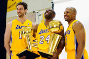 Kobe Bryant #24  of the Los Angeles Lakers laughs as he holds two NBA Finals Larry O'Brien Championship Trophy's as he poses for a photograph with teammates Pau Gasol #16 and Derek Fisher #2 during Media Day at the Toyota Center on September 25, 2010 in El Segundo, California. NOTE TO USER: User expressly acknowledges and agrees that, by downloading and/or using this Photograph, user is consenting to the terms and conditions of the Getty Images License Agreement.