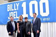 Billy Joel (2nd R) and wife Alexis Roderick, MSG CEO and chairman James Dolan (L), and New York Governor Andrew Cuomo pose in front of the banner honoring Joel's 100th Lifetime Performance at Madison Square Garden on July 18, 2018 in New York City.