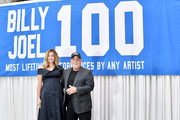 Billy Joel and wife Alexis Roderick pose in front of the banner during a press conference honoring Joel's 100th Lifetime Performance  at Madison Square Garden on July 18, 2018 in New York City.