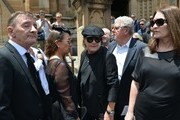 AC/DC lead singer Brian Johnson (C) and drummer Phil Rudd (L) gather after the funeral service for AC/DC co-founder Malcolm Young outside St. Mary's Cathedral in Sydney on November 28, 2017..Mourners bid farewell to AC/DC co-founder Malcolm Young on November 28, with his brother Angus carrying a guitar case as he led his coffin out of Sydney's St Mary's Cathedral. The legendary guitarist passed away earlier this month aged 64 after suffering from dementia for several years. / AFP PHOTO / PETER PARKS