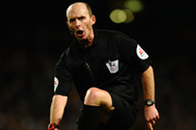 Referee Mike Dean points to his foot during the Barclays Premier League match between Manchester City and Chelsea at Etihad Stadium on February 3, 2014 in Manchester, England.