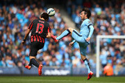 Suk-Young Yun of QPR heads the ball clear under pressure from David Silva of Manchester City during the Barclays Premier League match between Manchester City and Queens Park Rangers at the Etihad Stadium on May 10, 2015 in Manchester, England.