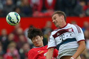 Alexander Zickler of Bayern Munich All Stars wins the ball ahead of Ji-sung Park of Manchester United Legends during the Manchester United Foundation charity match between Manchester United Legends and Bayern Munich All Stars at Old Trafford on June 14, 2015 in Manchester, England.