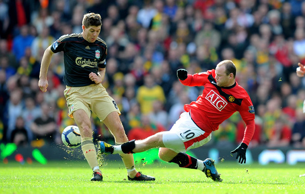 Steven Gerrard of Liverpool is tackled by Wayne Rooney of Manchester United during the Barclays Premier League match between Manchester United and Liverpool at Old Trafford on March 21, 2010 in Manchester, England.