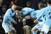 Manchester City's German midfielder Leroy Sane (2L) and Manchester City's Belgian midfielder Kevin De Bruyne (3L) celebrate after Manchester City's Spanish midfielder David Silva (L) scored the opening goal during the English Premier League football match between Manchester United and Manchester City at Old Trafford in Manchester, north west England, on December 10, 2017. / AFP PHOTO / Oli SCARFF / RESTRICTED TO EDITORIAL USE. No use with unauthorized audio, video, data, fixture lists, club/league logos or 'live' services. Online in-match use limited to 75 images, no video emulation. No use in betting, games or single club/league/player publications.  /