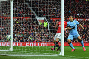 Sergio Aguero of Manchester City (R) scores their first goal during the Barclays Premier League match between Manchester United and Manchester City at Old Trafford on April 12, 2015 in Manchester, England.