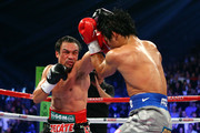 (L-R) Juan Manuel Marquez throws a left at Manny Pacquiao during their welterweight bout at the MGM Grand Garden Arena on December 8, 2012 in Las Vegas, Nevada.