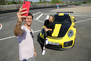 Porsche Brand Ambassadors Maria Sharapova and Mark Webber take a selfie after driving with the high performance sports car Porsche 911 RT2 RS on the Weissach race track before the start of the Porsche Tennis Grand Prix tennis tournament on April 20, 2018 in Stuttgart, Germany.