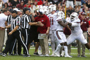 Referees separate head coach Dan Mullen of the Mississippi State Bulldogs  and head coach Mark Whipple of the Massachusetts Minutemen during an altercation after a play while Jessie Britt #5 and Ray Thomas-Ishman Sr. #57 of the Massachusetts Minutemen scuffle in the second half of an NCAA football game at Davis Wade Stadium on November 4, 2017 in Starkville, Mississippi.