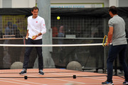 """Roger Federer and Rafael Nadal play on a mini court during the """"Match in Africa"""" photoshoot at Grand Parade on February 7, 2019 in Cape Town, South Africa."""
