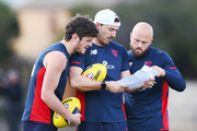 Angus Brayshaw (L) Michael Hibberd (C) and Nathan Jones of the Demons read paperwork during a Melbourne Demons AFL training session at Gosch's Paddock on September 3, 2018 in Melbourne, Australia.