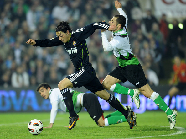 Mesut Ozil Mesut Ozil (L) of Real Madrid duels for the ball with Mehdi Lacen (R) of Racing Santander leaving Domingo Cisma behind during the la Liga match between Racing Santander and Real Madrid at El Sardinero stadium on March 6, 2011 in Santander, Spain.