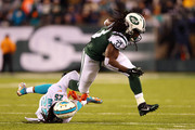 Chris Ivory #33 of the New York Jets runs the ball in the first half against Louis Delmas #25 of the Miami Dolphins during their game at MetLife Stadium on December 1, 2014 in East Rutherford, New Jersey.
