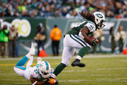 Chris Ivory #33 of the New York Jets runs against  Jamar Taylor #22 of the Miami Dolphins during their game at MetLife Stadium on November 29, 2015 in East Rutherford, New Jersey.