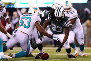 Chris Ivory #33 of the New York Jets recovers a fumble by Geno Smith #7 against Jelani Jenkins #53 of the Miami Dolphins in the fourth quarter during their game at MetLife Stadium on December 1, 2014 in East Rutherford, New Jersey.