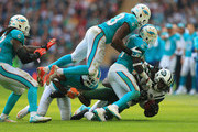Chris Ivory #33 of the New York Jets is tackled by Jelani Jenkins #53 of the Miami Dolphins and Michael Thomas #31 of the Miami Dolphins during the game at Wembley Stadium on October 4, 2015 in London, England.
