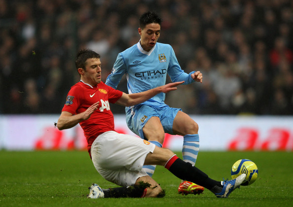 Michael Carrick Samir Nasri of Manchester City is challenged by Michael Carrick of Manchester United during the FA Cup Third Round match between Manchester City and Manchester United at the Etihad Stadium on January 8, 2012 in Manchester, England.