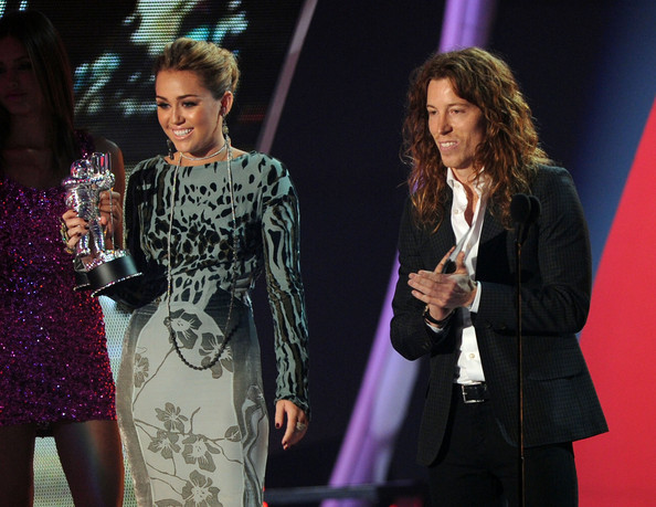 Miley Cyrus Singer Miley Cyrus (L) and snowboarder Shaun White speak onstage during the 2011 MTV Video Music Awards at Nokia Theatre L.A. LIVE on August 28, 2011 in Los Angeles, California.