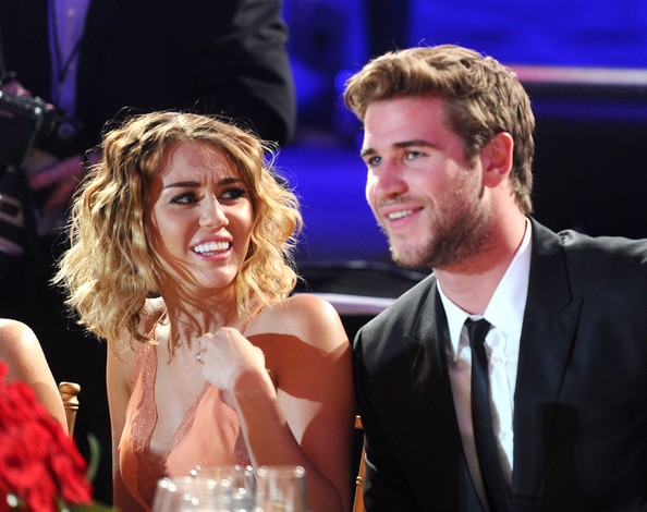Miley Cyrus Actress/singer Miley Cyrus (L) and actor Liam Hemsworth in the audience during Muhammad Ali's Celebrity Fight Night XIII held at JW Marriott Desert Ridge Resort & Spa on March 24, 2012 in Phoenix, Arizona.