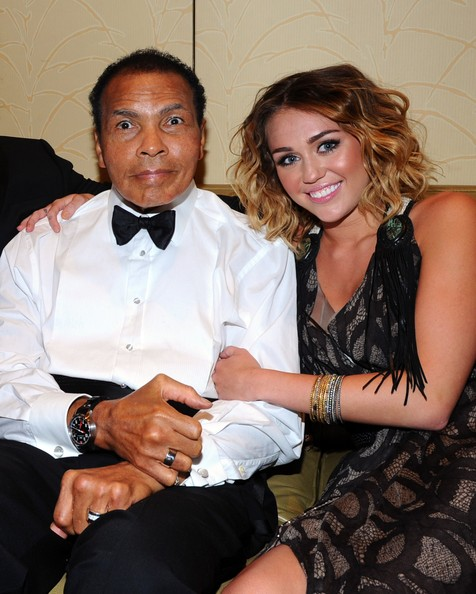 Miley Cyrus Muhammad Ali (L) and singer Miley Cyrus pose backstage during Muhammad Ali's Celebrity Fight Night XIII held at JW Marriott Desert Ridge Resort & Spa on March 24, 2012 in Phoenix, Arizona.