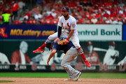 Greg Garcia #35 of the St. Louis Cardinals attempts to leap over Mike Moustakas #18 of the Milwaukee Brewers as he turns a double play during the eighth inning at Busch Stadium on August 19, 2018 in St Louis, Missouri.