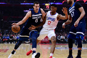 Jeff Teague #0 of the Minnesota Timberwolves drives on Tyrone Wallace #12 of the LA Clippers as Taj Gibson #67 looks on during the first half at Staples Center on January 22, 2018 in Los Angeles, California.