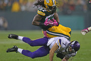 Christian Ponder #7 of the Minnesota Vikings tackles Jamari Lattimore #57 of the Green Bay Packers after an interception at Lambeau Field on October 2, 2014 in Green Bay, Wisconsin.