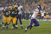 Quarterback Christian Ponder #7 of the Minnesota Vikings scrambles up the middle, past  Mike Pennel #64 of the Green Bay Packers, for a 6 yard touchdown in the forth quarter at Lambeau Field on October 2, 2014 in Green Bay, Wisconsin. Packers defeat Vikings 42-10.