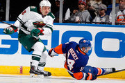 Cody McCormick #8 of the Minnesota Wild sends Thomas Hickey #14 of the New York Islanders to the ice during an NHL hockey game at Nassau Veterans Memorial Coliseum on March 18, 2014 in Uniondale, New York.