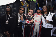 Austin Dillon, driver of the #3 Dow Coating Chevrolet, and Darrell Wallace Jr., driver of the #43 Farmer John Chevrolet, pose for a photo with Migos prior to the Monster Energy NASCAR Cup Series Auto Club 400 at Auto Club Speedway on March 18, 2018 in Fontana, California.