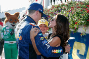 Kyle Busch, driver of the #18 M&M's Caramel Toyota, his wife, Samantha, and their son, Brexton, celebrate in Victory Lane after winning the Monster Energy NASCAR Cup Series Gander Outdoors 400 at Pocono Raceway on July 29, 2018 in Long Pond, Pennsylvania.