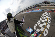 Kyle Busch, driver of the #18 M&M's Hazelnut Toyota, crosses the finish line to win the Monster Energy NASCAR Cup Series Pocono 400 at Pocono Raceway on June 02, 2019 in Long Pond, Pennsylvania.