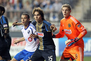 Midfielder Felipe Martins #7 of the Montreal Impact fights for position with midfielder Gabriel Farfan #15 and goalkeeper Zac MacMath #18 of the Philadelphia Union during a game at PPL Park on July 14, 2012 in Chester, Pennsylvania. The Union won 2-1.