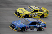 Dale Earnrhardt Jr., driver of the #88 Nationwide Plenti Chevrolet, races Matt Kenseth, driver of the #20 Dollar General Toyota, during the NASCAR Sprint Cup Series AAA 400 at Dover International Speedway on October 4, 2015 in Dover, Delaware.