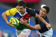 Michael Adams of the Rays is tackled by Anthony Faingaa of Queensland Country during the round four National Rugby Championship match between Queensland Country and the North Harbour Rays at Cbus Super Stadium on September 13, 2014 in Gold Coast, Australia.
