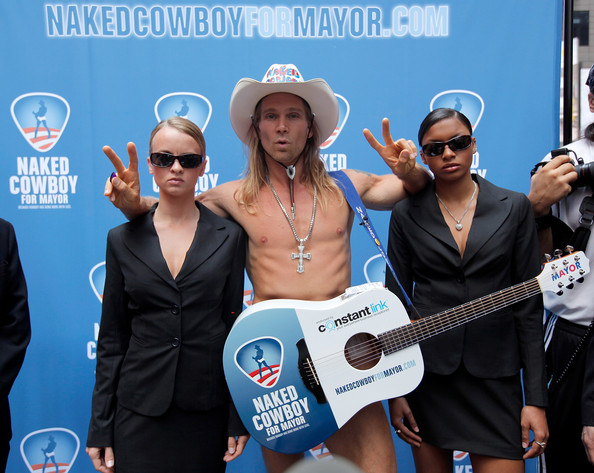 "Actor/ local New  York personality Robert John Burck (C) also known as ""The Naked Cowboy"" poses with his security detail following a press conference announcing the launch the Naked Cowboy's New York City mayoral campaign at Military Island, Times Square on July 22, 2009 in New York City."