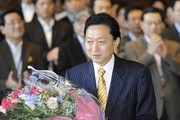 Outgoing Prime Minister Yukio Hatoyama receives a bouquet of flowers from a member of staff at his office as he leaves his official residence on June 4, 2010 in Tokyo, Japan. Hatoyama served as Prime Minister from September 2009, but resigned in June 2010. He will be succeeded by Naoto Kan.