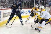 Blake Wheeler #26 of the Winnipeg Jets moves the puck against Ryan Ellis #4 and Nick Bonino #13 of the Nashville Predators in Game Four of the Western Conference Second Round during the 2018 NHL Stanley Cup Playoffs on May 3, 2018 at Bell MTS Place in Winnipeg, Manitoba, Canada. (Photo by Jason Halstead /Getty Images) *** Local Caption *** Blake Wheeler; Ryan Ellis; Nick Bonino