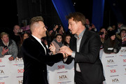 Nicky Byrne from Westlife greets John Barrowman as they attend the National Television Awards held at the O2 Arena on January 22, 2019 in London, England.