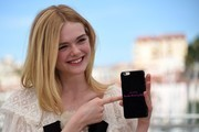 "US actress Elle Fanning shows the back of her mobile phone on May 20, 2016 which reads ""directed by Nicolas Winding Refn"" during a photocall for the film ""The Neon Demon"" at the 69th Cannes Film Festival in Cannes, southern France.  / AFP / ANNE-CHRISTINE POUJOULAT"
