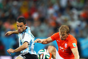 Maxi Rodriguez of Argentina and Dirk Kuyt of the Netherlands compete for the ball during the 2014 FIFA World Cup Brazil Semi Final match between the Netherlands and Argentina at Arena de Sao Paulo on July 9, 2014 in Sao Paulo, Brazil.