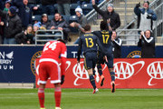 C.J. Sapong #17 and Chris Pontius #13 of Philadelphia Union run towards the crowd celebrating as Lee Nguyen #24 of New England Revolution looks down at Talen Energy Stadium on March 20, 2016 in Chester, Pennsylvania.