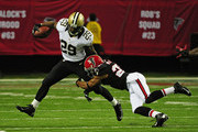 Chris Ivory #29 of the New Orleans Saints is tackled by Robert McClain #27 of the Atlanta Falcons at the Georgia Dome on November 29, 2012 in Atlanta, Georgia