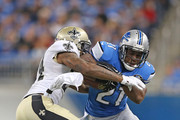 Reggie Bush #21 of the Detroit Lions tries to avoid the tackle by Corey White #24 of the New Orleans Saints in the second quarter at Ford Field on October 19, 2014 in Detroit, Michigan.