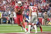 Wide receiver Larry Fitzgerald #11 of the Arizona Cardinals runs in a thirteen yard touchdown against defensive back Brandon Dixon #25 of the New York Giants in the first half at University of Phoenix Stadium on December 24, 2017 in Glendale, Arizona.
