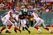 Chris Ivory #33 of the New York Jets runs the ball against Jameel McClain #53 of the New York Giants during a preseason game at MetLife Stadium on August 22, 2014 in East Rutherford, New Jersey.