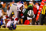 Bennett Jackson #36 and Charles James #37 of the New York Giants tackle Chris Ivory #33 of the New York Jets during a preseason game at MetLife Stadium on August 22, 2014 in East Rutherford, New Jersey.