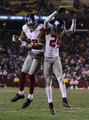 (R-L) Terrell Thomas #24 of the New York Giants and Osi Umenyiora #72 celebrate after Thomas scored on an interception return for a touchdown in the third quarter against  the Washington Redskins at FedEx Field on December 21, 2009 in Landover, Maryland.