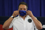 New York Governor Andrew Cuomo puts on a mask as he is joined by Rosie Perez and Chris Rock at a press conference where the two performers helped to promote coronavirus testing, social distancing and the use of a face mask on May 28, 2020 in New York City.  The news conference was held at the Madison Square Boys and Girls Club in the Flatbush, Brooklyn neighborhood, one of the hardest hit by Covid-19 in New York City.