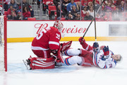 Brady Skjei #76 of the New York Rangers gets tripped by Frans Nielsen #51 of the Detroit Red Wings and they slide into goaltender Jimmy Howard #35 of the Wings during an NHL game at Little Caesars Arena on December 29, 2017 in Detroit, Michigan. The Wings defeated the Rangers 3-2 in a shootout.